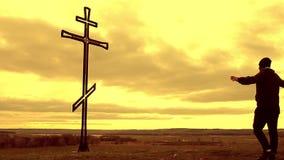 Άτομο σκιαγραφιών πάνω από το βουνό που εξετάζει με την ελπίδα το χριστιανικό σταυρό Ένα άτομο που κάνει μια ομολογία στο σταυρό, απόθεμα βίντεο