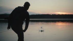 Άτομο σκιαγραφιών που ρίχνει τις πέτρες στο ηλιοβασίλεμα λιμνών απόθεμα βίντεο