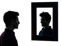 Άτομο σοβαρό μπροστά από τη σκιαγραφία καθρεφτών του Στοκ Εικόνες