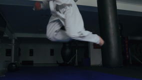 Άτομο στα άσπρα ομοιόμορφα πόδια κατάρτισης με punching την τσάντα στη γυμναστική αργά φιλμ μικρού μήκους