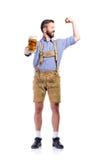 Άτομο στα βαυαρικά ενδύματα, που κρατά την μπύρα, που παρουσιάζει δικέφαλους μυς Στοκ εικόνα με δικαίωμα ελεύθερης χρήσης