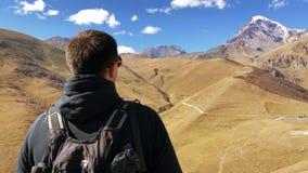 Άτομο στα βουνά ενάντια σε έναν σαφή ουρανό μια ηλιόλουστη ημέρα φιλμ μικρού μήκους