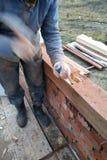 Άτομο στα γάντια, εργασία με ένα σφυρί και λίγο της ξύλινης επεξεργασίας στοκ εικόνες με δικαίωμα ελεύθερης χρήσης