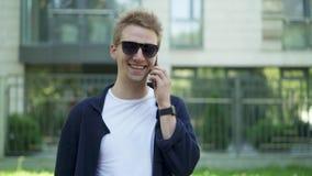 Άτομο στα γυαλιά ηλίου που γελά μιλώντας στο smartphone φιλμ μικρού μήκους