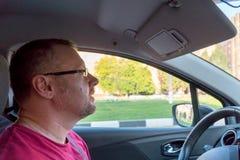 Άτομο στα γυαλιά με μια γενειάδα στη ρόδα του αυτοκινήτου στοκ εικόνες