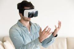 Άτομο στα γυαλιά κασκών εικονικής πραγματικότητας που εξετάζει τα χέρια του Στοκ Εικόνες