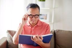 Άτομο στα γυαλιά που διαβάζει το βιβλίο στο σπίτι Στοκ Φωτογραφίες