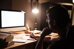 Άτομο στα γυαλιά που κάθονται και που χρησιμοποιούν τον υπολογιστή για τη μελέτη στοκ εικόνα