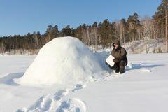Άτομο στα θερμά ενδύματα που στηρίζεται μια παγοκαλύβα σε ένα χιονώδες ξέφωτο το χειμώνα, Σιβηρία, Ρωσία στοκ φωτογραφία με δικαίωμα ελεύθερης χρήσης