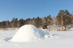 Άτομο στα θερμά ενδύματα που στηρίζεται μια παγοκαλύβα σε ένα χιονώδες ξέφωτο το χειμώνα, Σιβηρία, Ρωσία στοκ φωτογραφίες με δικαίωμα ελεύθερης χρήσης