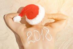 Άτομο στα καπέλα Santa με την επιγραφή 2018 στην πλάτη που βρίσκεται επάνω Στοκ εικόνες με δικαίωμα ελεύθερης χρήσης