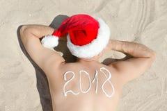 Άτομο στα καπέλα Santa με την επιγραφή 2018 στην πλάτη που βρίσκεται επάνω Στοκ Εικόνες