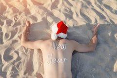 Άτομο στα καπέλα Santa με το νέο έτος επιγραφής στον πίσω lyin Στοκ εικόνες με δικαίωμα ελεύθερης χρήσης