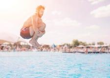 Άτομο στα μπλε και κόκκινα σορτς που πηδά στην πισίνα στην ηλιόλουστη ημέρα Απόλαυση του κόμματος λιμνών με τους φίλους στοκ εικόνα