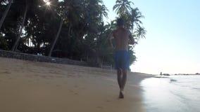 Άτομο στα μπλε τρεξίματα σορτς κατά μήκος της ακτής στον ατελείωτο ωκεανό φιλμ μικρού μήκους