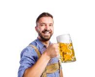 Άτομο στα παραδοσιακά βαυαρικά ενδύματα που πίνει την μπύρα Στοκ Φωτογραφία