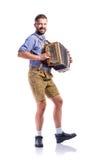 Άτομο στα παραδοσιακά βαυαρικά ενδύματα που παίζει το ακκορντέον Oktoberfe Στοκ Φωτογραφία