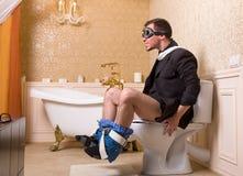 Άτομο στα πειραματικά γυαλιά που κάθεται στο κύπελλο τουαλετών Στοκ Φωτογραφίες