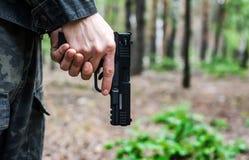 Άτομο στα στρατιωτικά ενδύματα που κρατά ένα πυροβόλο όπλο κάτω στοκ φωτογραφίες