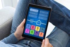 Άτομο στα τζιν που κάθεται την ταμπλέτα εκμετάλλευσης με app το έξυπνο σπίτι Στοκ εικόνες με δικαίωμα ελεύθερης χρήσης