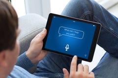 Άτομο στα τζιν που κρατά την ταμπλέτα με app την προσωπική βοηθητική οθόνη Στοκ φωτογραφία με δικαίωμα ελεύθερης χρήσης