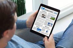 Άτομο στα τζιν που κρατά τον υπολογιστή ταμπλετών με app τις παγκόσμιες ειδήσεις Στοκ φωτογραφίες με δικαίωμα ελεύθερης χρήσης