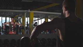 Όμορφος μυϊκός νεαρός άνδρας που ασκεί τους δικέφαλους μυς στη γυμναστική με τους αλτήρες απόθεμα βίντεο