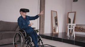 Άτομο στην αναπηρική καρέκλα χρησιμοποιώντας το τρισδιάστατο κράνος vr και περνώντας το ελεύθερο χρόνο απόθεμα βίντεο