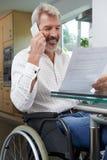 Άτομο στην αναπηρική καρέκλα που κάνει το τηλεφώνημα ενώ επιστολή ανάγνωσης στοκ φωτογραφίες
