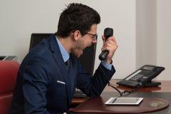 Άτομο στην επίσημη ένδυση που φωνάζει στο τηλέφωνο Στοκ φωτογραφία με δικαίωμα ελεύθερης χρήσης