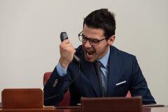Άτομο στην επίσημη ένδυση που φωνάζει στο τηλέφωνο Στοκ Φωτογραφία