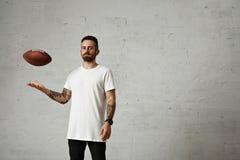 Άτομο στην κενή άσπρη μπλούζα με ένα εκλεκτής ποιότητας ποδόσφαιρο στοκ φωτογραφία