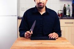 Άτομο στην κουζίνα με το μαχαίρι και τον τεμαχίζοντας πίνακα Στοκ φωτογραφίες με δικαίωμα ελεύθερης χρήσης