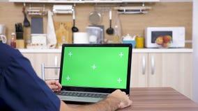 Άτομο στην κουζίνα που εξετάζει το lap-top με την πράσινη χλεύη οθόνης επάνω απόθεμα βίντεο
