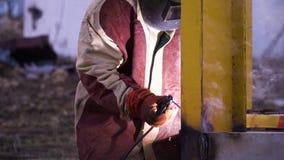 Άτομο στην κόκκινη και γκρίζα τήβεννο που ενώνει στενά την κίτρινη κατασκευή μετάλλων στα γάντια ασφάλειας και τη μάσκα ασφάλειας απόθεμα βίντεο