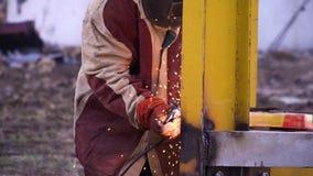 Άτομο στην κόκκινη και γκρίζα τήβεννο που ενώνει στενά την κίτρινη κατασκευή μετάλλων στα γάντια ασφάλειας και τη μάσκα ασφάλειας φιλμ μικρού μήκους