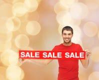 Άτομο στην κόκκινη μπλούζα με το σημάδι πώλησης Στοκ εικόνες με δικαίωμα ελεύθερης χρήσης