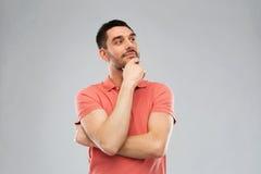Άτομο στην μπλούζα πόλο που σκέφτεται πέρα από το γκρίζο υπόβαθρο Στοκ Φωτογραφίες