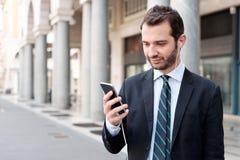 Άτομο στην πόλη που εξετάζει το έξυπνο τηλέφωνό του Στοκ εικόνα με δικαίωμα ελεύθερης χρήσης