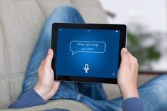 Άτομο στην ταμπλέτα εκμετάλλευσης καναπέδων με app την προσωπική βοηθητική οθόνη Στοκ εικόνες με δικαίωμα ελεύθερης χρήσης