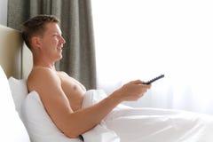 Άτομο στην τηλεόραση προσοχής κρεβατιών και TV εκμετάλλευσης μακρινή Στοκ Εικόνα
