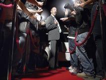 Άτομο στην τοποθέτηση κόκκινου χαλιού μπροστά από τα παπαράτσι στοκ φωτογραφία