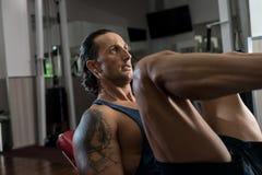 Άτομο στη γυμναστική στην άσκηση μηχανών Στοκ Εικόνες