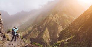 Άτομο στη δύσκολη κάνοντας εικόνα μεγάλου υψομέτρου του τοπίου βουνών μπροστά από ένα βαθύ φαράγγι Το θερμό φως ήλιων γέμισε Στοκ Φωτογραφίες