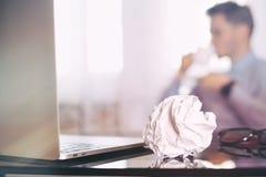 Άτομο στη θαμπάδα, lap-top, φλυτζάνι καφέ και τσαλακωμένος wads στον πίνακα νέα ιδέα στοκ φωτογραφία με δικαίωμα ελεύθερης χρήσης