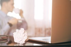 Άτομο στη θαμπάδα, lap-top, φλυτζάνι καφέ και τσαλακωμένος wads στον πίνακα E στοκ φωτογραφίες με δικαίωμα ελεύθερης χρήσης