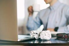 Άτομο στη θαμπάδα, lap-top, φλυτζάνι καφέ και τσαλακωμένος wads στον πίνακα νέα ιδέα στοκ εικόνες