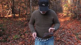 Άτομο στη μάσκα αποκριών, ακονίζοντας μαχαίρι στο τσεκούρι απόθεμα βίντεο