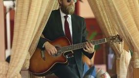 Άτομο στη μαύρη κιθάρα παιχνιδιών κοστουμιών sensually μεταξύ των κουρτινών απόθεμα βίντεο