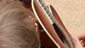 Άτομο στη μαύρη κιθάρα παιχνιδιών κοστουμιών sensually φιλμ μικρού μήκους